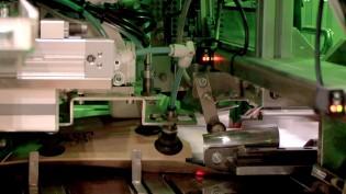 段ボール封筒に商品を自動で梱包するメール便自動梱包機